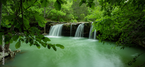 Soft ethereal waterfall from the Ozark Mountains deep in the Arkansas forest. The majestic waterfall is named falling water falls. The cascade drops into a turquoise, emerald pool of water © Thorin Wolfheart