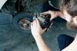 A car mechanic installing new brake pads on a car wheel hub