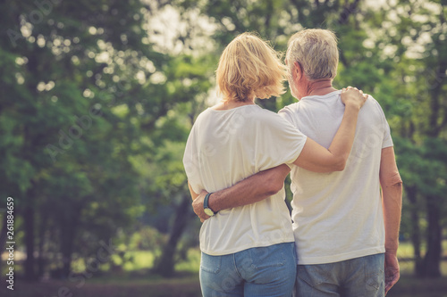 Photo  Elder man and woman embrace together looking into the green park