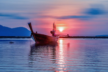 Small Fishing Boat In Sea During Sunrise