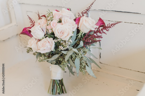 Pink roses and Calla Lily bridal bouquet on white vintage wall