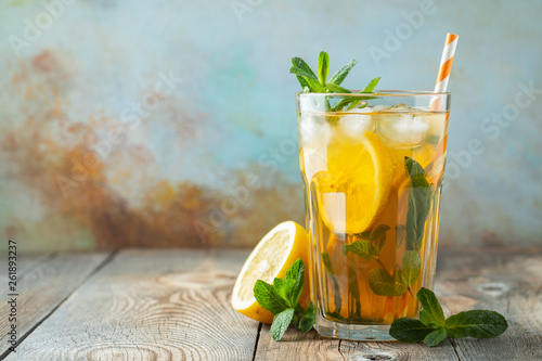 Fotografia  Traditional iced tea with lemon and ice in tall glass on a wooden rustic table