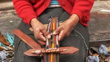 Peruvian Woman Weaving On A St...
