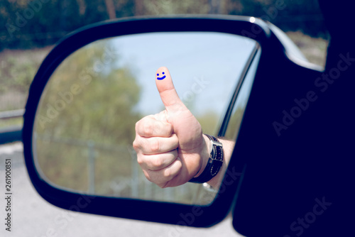 Valokuva  Ein Mann, Daumen hoch und ein Lächeln gemalt auf dem Finger