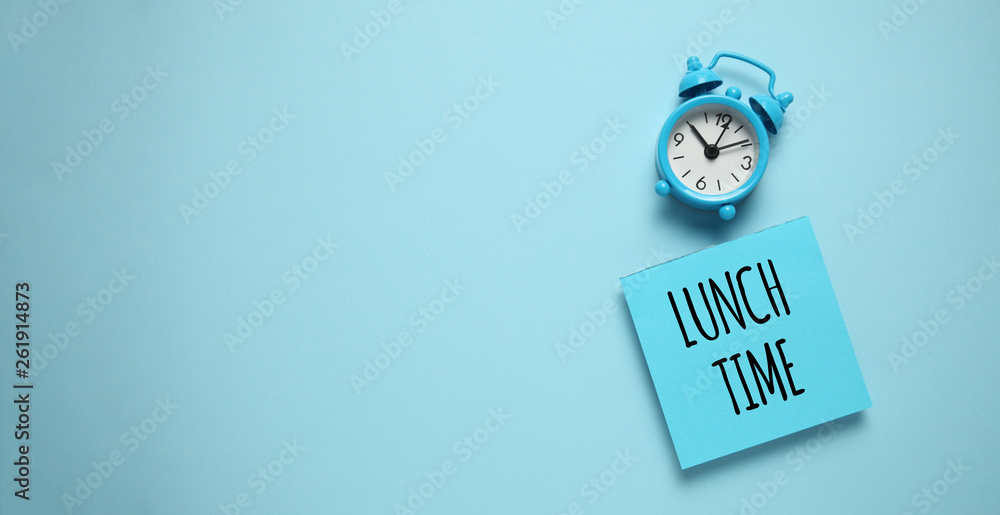 Fototapeta Blue alarm clock and paper reminder lunch time.