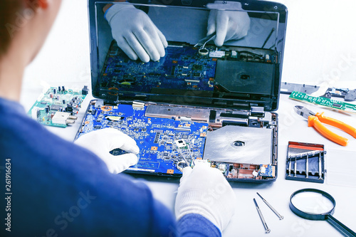 Computer Repair. Tech fixes motherboard in service center.