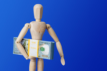 Wooden Toy Figure With Money On Blue