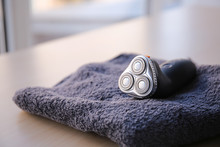 Towel With Electric Shaver On Table