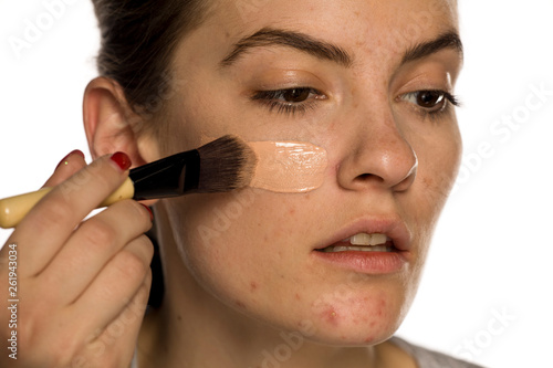 Young freckled woman applying liquid foundation on white background Canvas Print