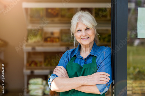 Fotomural  Portrait of confident owner with arms crossed standing in small grocery store