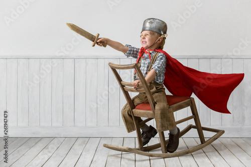 Fotografiet  Little boy plays the knight