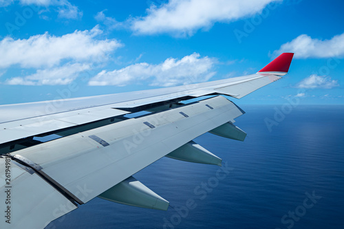 Leinwand Poster wing of an airplane aero plane with landing flaps blue cloudy sky