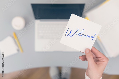 Foto Woman clerk sitting holding note paper sticker with Welcome word