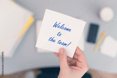 Fototapeta  Woman clerk sitting holding note paper sticker with welcome to the team phrase