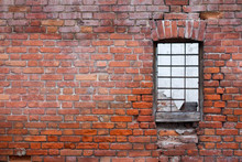 Window With Bars On The Background Of The Brick Wall Of The Old House