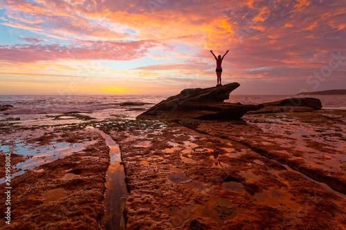 Foto auf Leinwand Violett rot Woman standing on coastal rocks with stunning sunrise and reflections