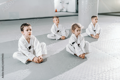 Obrazy Taekwondo   small-group-of-caucasian-sporty-kids-sitting-on-floor-at-taekwondo-training-an-listening-to-their-trainer