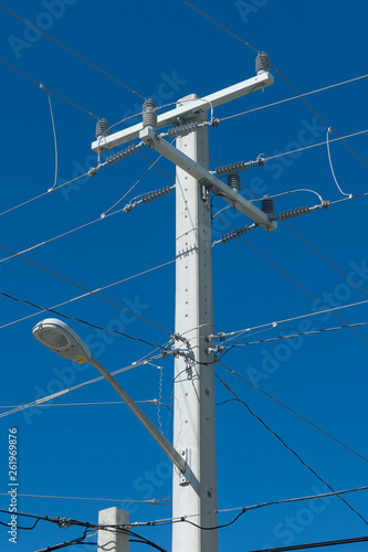 Fotografie, Obraz  power lines and a street light at pole in front of blue sky