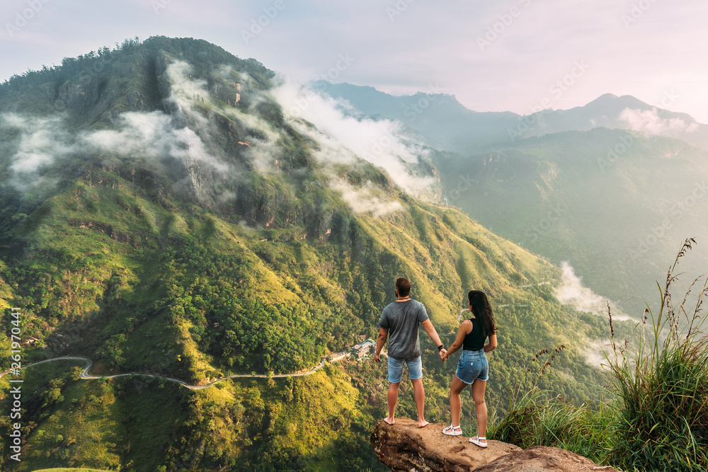 Fototapety, obrazy: The couple greets the sunrise in the mountains. Man and woman in the mountains. Man and woman holding hands. The couple travels around Asia. Travel to Sri Lanka. Serpentine in the mountains. Honeymoon