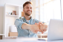 Portrait Of Handsome Young Man  Stretching At Workplace In Office And Smiling Happily, Copy Space