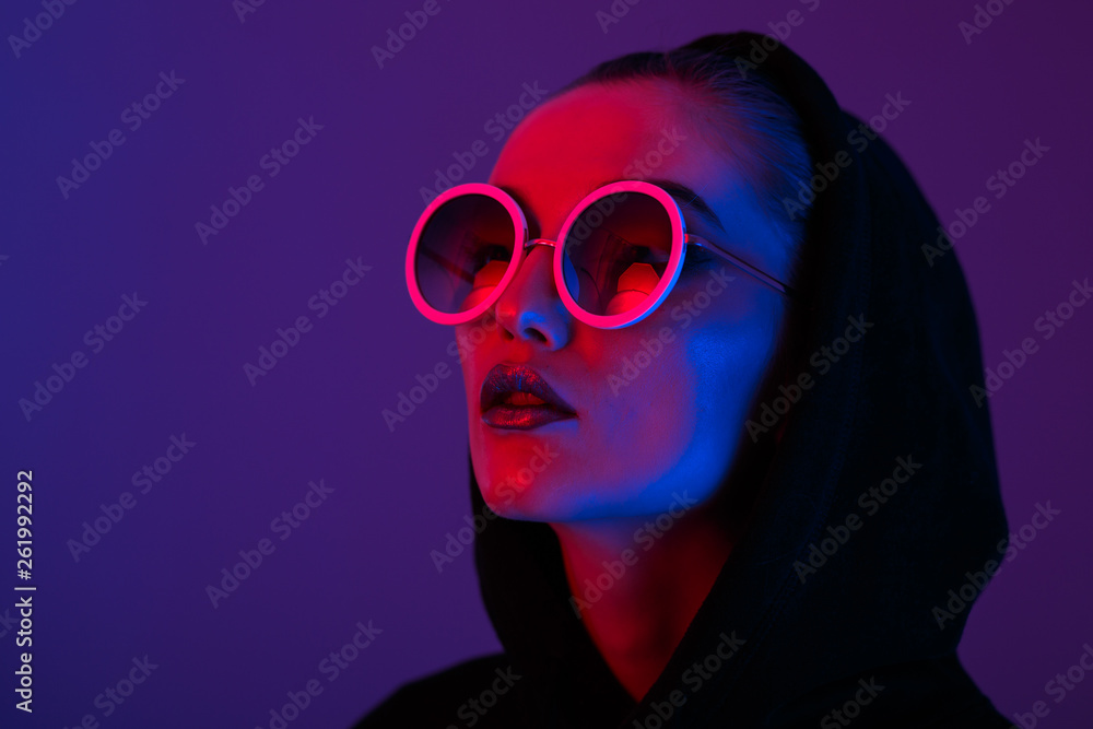 Fototapeta Portrait of fashion young girl in a black sweater with a hood and round sunglasses in red and blue neon light in the studio