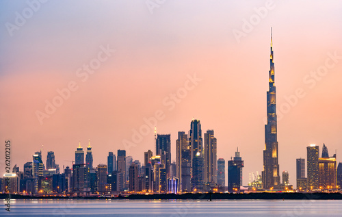 Canvas Stunning view of the illuminated Dubai skyline during sunset with the magnificent Burj Khalifa and many other buildings and skyscrapers reflected on a silky smooth water flowing in the foreground