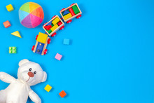 Baby Kids Toys Background. White Teddy Bear, Wooden Train, Colorful Blocks On Blue Background