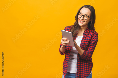 Photo  Portrait with copy space empty place of pretty charming confident smiling woman in casual having tablet in hands isolated on yellow background