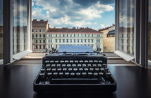 Workplace Of A Writer, Journalist, Creator. Old Typewriter On The Table Against The Background Of Ancient City Buildings. Retro Style. The Concept On Scientific, Historical, Literature Topics.