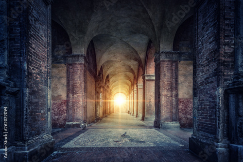 Rays of divine light illuminate old arches and columns of ancient buildings. Bologna, Italy. Conceptual image on historical, religious and travel theme.