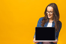 Surprised Happy Brunette Woman In Casual Showing Blank Laptop Computer Screen And Pointing On It While Looking At The Camera With Open Mouth Over Yellow Background.