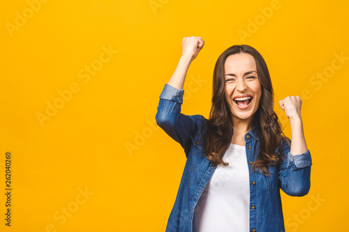 I'm winner! Happy successful young woman with raised hands shouting and celebrating success over yellow background Canvas Print
