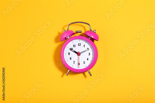Photo  Pink alarm clock on yellow background. Minimalism concept