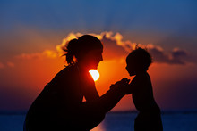 Happy Family Black Silhouette On Sunset Sky Background. Young Mother, Baby Son Have Fun Together, Walk By Sea Beach. Barefoot Child Look At Sun. Travel Lifestyle, Parents With Kids On Summer Vacation.