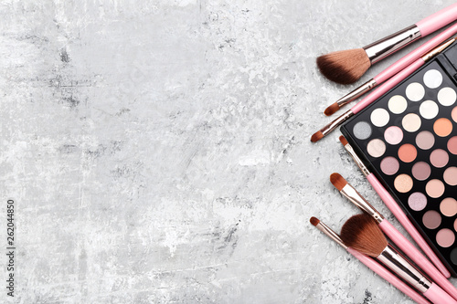 Fotografía  Makeup brushes with palette on grey background