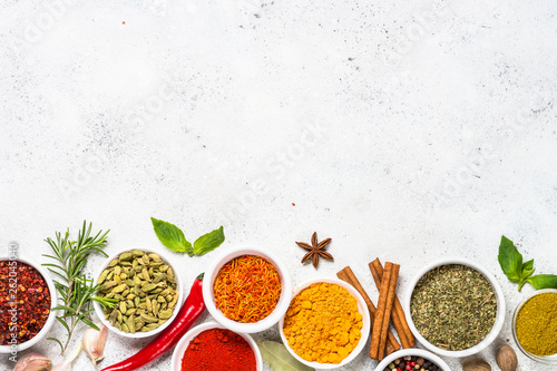 Photo  Spices and herbs on white stone table.