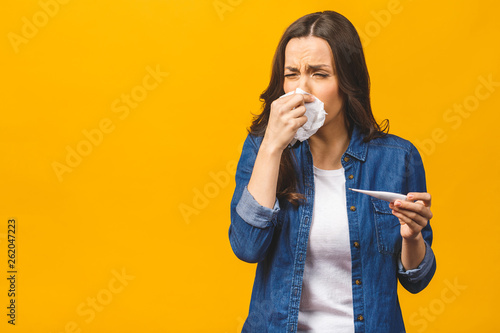 Fotografija Young woman having flue taking thermometer