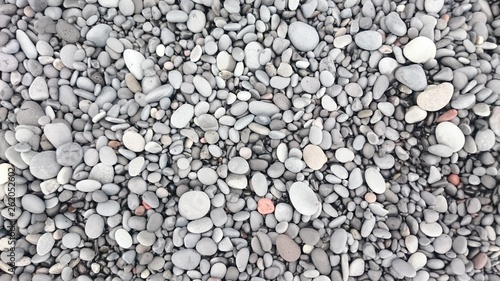 Foto op Plexiglas Stenen in het Zand Background with lots of smooth stones on a rocky beach