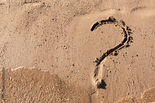 Question mark sign on sand beach near the sea Fototapeta