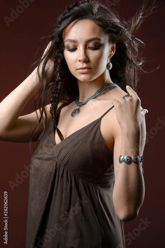 Beauty portrait of a brunette in jewelry on brown background.