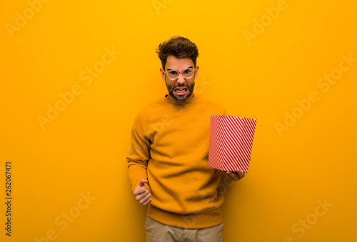 Valokuva  Young man holding popcorns screaming very angry and aggressive