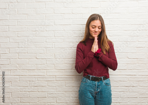 Photo  Young cool woman over a bricks wall praying very happy and confident