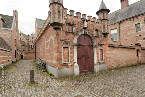 Brick walls, doors and towers of historical houses in Beguinage, 13th century co Wallpaper Mural