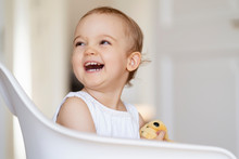 Portrait Of Laughing Toddler Girl Sitting On A Chair With Cuddling Toy