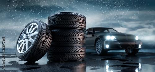 Valokuvatapetti Reifenstapel mit Auto im Regen 2