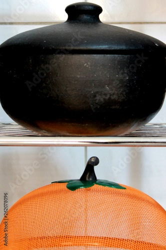 Fotografiet  Detail of the composition of a metal shelf, an antique pan and an orange basket of fruits and vegetables, in a kitchen of a house in the city of São Paulo, Brazil