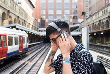 Young Man Listening Music With Headphones, Standing On Station