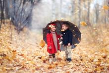 Boy And Girl Children Under Umbrella In Autumn