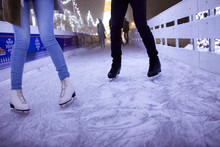 Legs Of Couple Ice Skating On An Ice Rink At Night