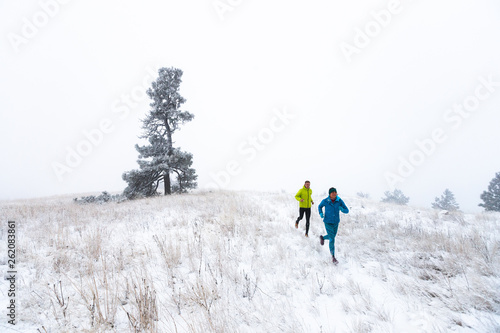 Woman and man running in winter, Idaho